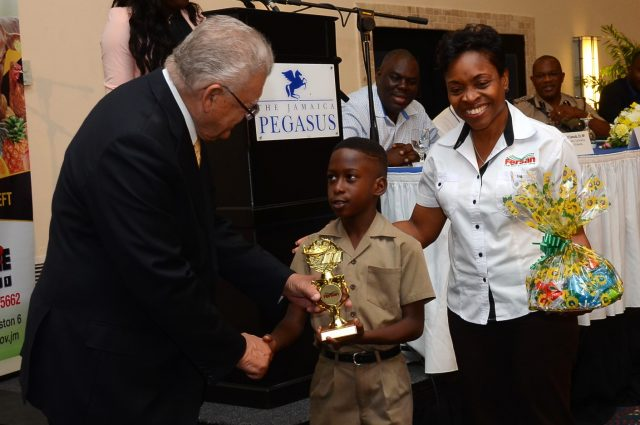 Minister of Industry, Commerce, Agriculture and Fisheries, Hon. Karl Samuda, presents the Ministry's trophy to Asher Harrison of Greater Portmore Primary School, who was the winner in the primary school category of the Praedial Larceny Prevention Unit (PLPU) inaugural essay competition in 2016. Sharing the moment is Marketing Coordinator at Newport Fersan, Joan Sharpe Colley.