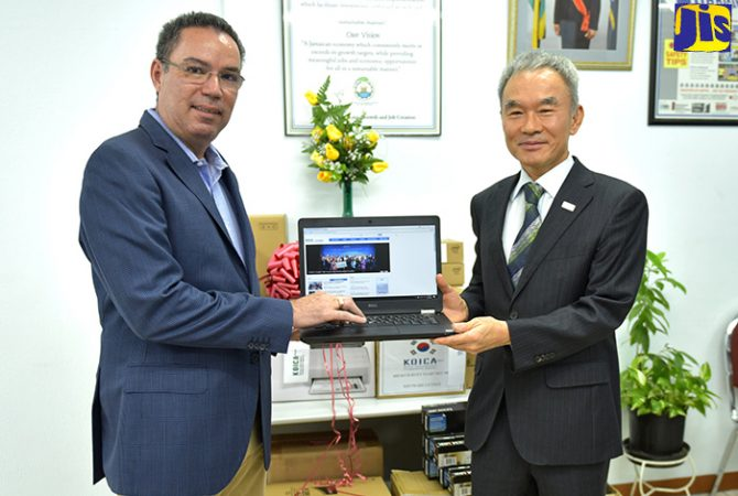 Minister without Portfolio in the Ministry of Economic Growth and Job Creation, Hon. Daryl Vaz (left), accepts a laptop computer from Chargé d' Affaires, Embassy of the Republic of Korea, Young Gyu Lee, at the Land Administration and Management Division in Kingston on Friday (February 23). Equipment, valued at US$85,000, has been donated by the Government of the Republic of Korea, to improve Jamaica's efficiency in cadastral mapping and land registration.