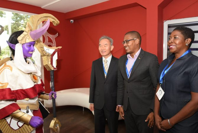 State Minister for Education, Youth and Information, Hon. Floyd Green (second right), observes as cosplayer, Rhea Rampair, demontrates her portrayal of Soraka, the Starchild from the videogame League of Legends. Occasion was the opening day of the two-day Jamaica Digital Screen Business Conference, at the Spanish Court Hotel in New Kingston, on May 24. Others from (second left) are Chargé d'Affaires of the Embassy of the Republic of Korea in Jamaica, Ambassador Young Gyu Lee and World Bank's Co-Task Team Leader for the Youth Employment in the Digital Animation Industry (YEDAI) Project, Karlene Francis.