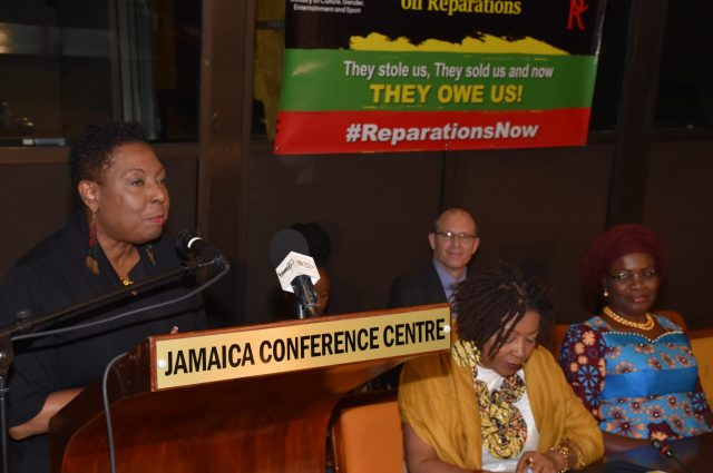 Minister of Culture, Gender, Entertainment and Sport, Hon. Olivia Grange (at podium), speaks at Reparation Youth Conference, held at the Jamaica Conference Centre in downtown, Kingston, on Friday (May 25). Seated (from left) are: Co-Chair, National Council on Reparations in Jamaica, Professor Verene Shepherd and Nigerian High Commissioner to Jamaica, Her Excellency Janet Olisa. In the background is Charge D'Affaires at the South African High Commission, Mr. Phillip Riley.