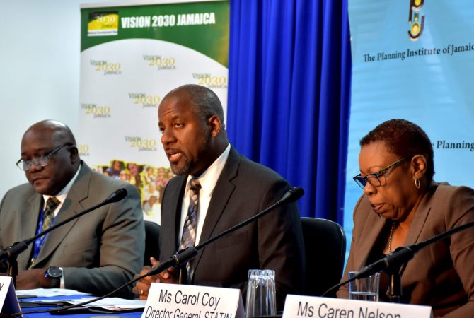 Planning Institute of Jamaica (PIOJ) Director General, Dr. Wayne Henry (centre), addressing journalists during the Agency's quarterly media briefing on May 22. Listening (from left) are Senior Director for the PIOJ's Economic Planning, Research and Policy Logistics Division, James Stewart; and Statistical Institute of Jamaica Director General, Carol Coy.