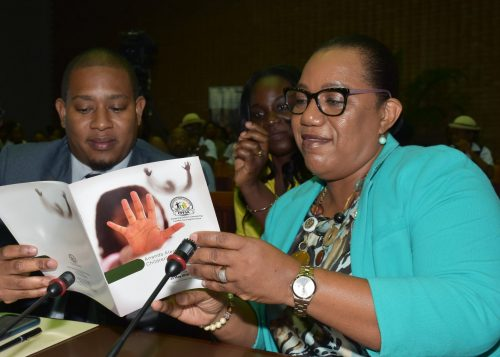 State Minister for Education, Youth and Information, Hon. Floyd Green (left), and Chief Executive Officer (CEO) of the Child Protection and Family Services Agency (CPFSA), Rosalee Gage-Grey (right), discussing the programme for the National Missing Children's Forum with Public Relations Officer of the CPFSA, Jeneva Gordon, at the Jamaica Conference Centre in Kingston on May 25.