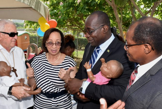 Minister of Education, Youth and Information, Senator the Hon. Ruel Reid (second right) and Opposition Spokesman on Education and Training, Reverend Ronald Thwaites (left), hold dummy babies at the launch of the Jamaica Brain Builders Programme, at the University of Technology (UTech) on Friday (July 6), while Professor for Child Health, Child Development and Behaviour, University of the West Indies, Mona, Professor Maureen Samms-Vaughn (second left), speaks with them. Sharing in the moment is Deputy President, University of Technology (UTech), Professor Colin Gyles (right).