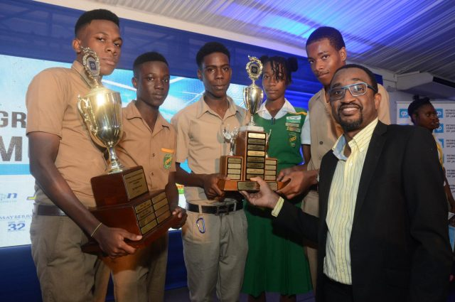 PCJ Winners: Petroleum Corporation of Jamaica (JCJ) Special Projects Manager, Peter Ruddock (right), presents the winning trophy in the 2017/18 PCJ Schools Energy Programme Competitionton to students of Winston Jones High School in Manchester. The are (from left) Ruchshane Williamson, Okelo Smith, Shawn Clarke, Kadine Jordine and Christopher Morgan. The awards ceremony was held recently at the Spanish Court Hotel in New Kingston.