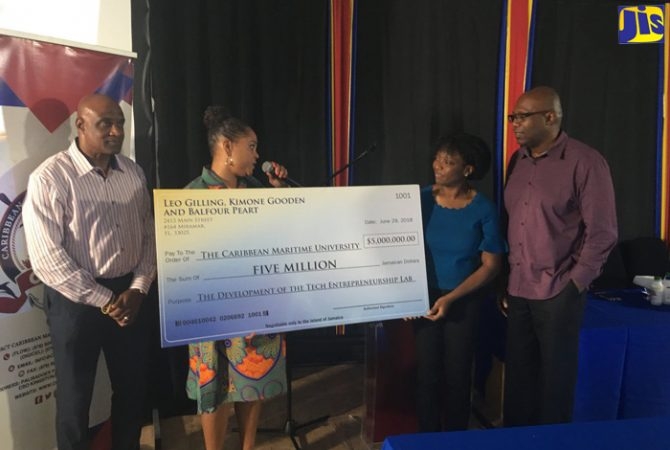 Executive Director at the Centre for Digital Innovation at the Caribbean Maritime University (CMU), Erica Simmons (second left), accepts a cheque for $5 million from partners in the Jamaica Diaspora Investment Group – Kimone Gooden (second right) and Leo Gilling (right), for the establishment of a technology entrepreneurship lab at the CMU. The presentation was made at the university's campus in Kingston recently. Looking on is President of the CMU, Dr. Fritz Pinnock.