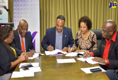 Attorney General and Member of Parliament for St. James West Central, Marlene Malahoo Forte (second right), and Managing Director, Jamaica Social Investment Fund (JSIF), Omar Sweeney (centre), sign contracts for JSIF's 2018 summer camps, at the agency's Oxford Road offices in St. Andrew on July 27. Others participating in the signing (from left) are Social Development Manager, JSIF, Mona Sue-Ho; Executive Director, Operation Friendship, Rev. Dr. Webster Edwards; and Acting Assistant Commissioner of Police, Steve McGregor. The camps are being implemented by JSIF under its World Bank-funded Integrated Community Development Project (ICDP).