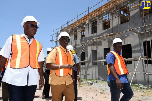 Local Government and Community Development Minister, Hon. Desmond McKenzie (centre) converses with Portmore Mayor, Leon Thomas (left), during a tour of the new Portmore Municipal Corporation building site in St. Catherine on Friday (July 27). At right is Project Officer at the municipal corporation, Anthony Wilson.