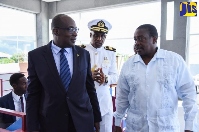 Minister of Education, Youth and Information, Senator the Hon. Ruel Reid (left), speaks with Minister of Transport and Mining, Hon. Robert Montague, at the launch of the Women in Maritime Association Caribbean (WiMAC) SeaPerch Underwater Robotics Programme at the Caribbean Maritime University (CMU) in Kingston on Thursday (September 27). In the background is President of the CMU, Professor Fritz Pinnock.