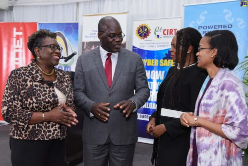 Acting Permanent Secretary in the Ministry of Science and Technology, Wahkeen Murray (right), is in discussion with Head, Counter-Terrorism and Organised Crime Investigation Branch, Jamaica Constabulary Force (JCF), Assistant Commissioner of Police (ACP), Fitz Bailey (second left) during the launch of Cybersecurity Awareness Month at the Spanish Court Hotel in New Kingston on September 27. Others (from left) are Director of Public Prosecutions, Paula Llewellyn; and Head, Jamaica Cyber Incident Response Team, Dr. Moniphia Hewling.