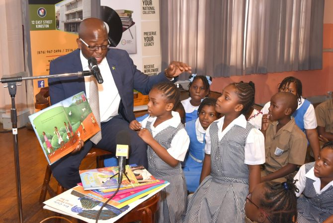 State Minister in the Ministry of Foreign Affairs and Foreign Trade, and Chairman of the Youth Advisory Committee of the Jamaica National Commission for UNESCO, Senator the Hon. Pearnel Charles Jr., reading to students during an International Literacy Day event at the Institute of Jamaica (IOJ), downtown Kingston on September 7. International Literacy Day will be observed globally on September 8.