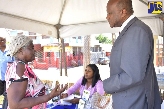 Executive Director of the Legal Aid Council, Hugh Faulkner (right), listens to Allman Town resident, Sylvia Rowe (left), at a justice fair in the community on September 28. At centre is Legal Consultant, Shara-Kay Dacres-Moore.