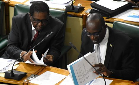 Minister of Education, Youth and Information, Senator the Hon. Ruel Reid (right), looks through his notes during Friday's (Sept. 28) sitting of the Upper House. At left is Government Senator Ransford Braham.