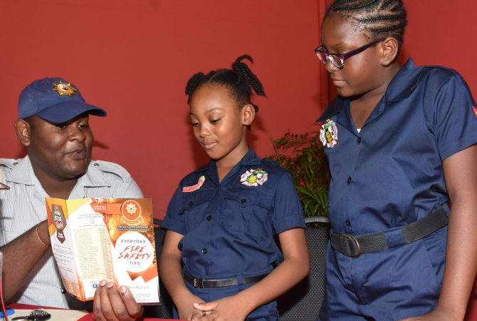 Firefighter of the Jamaica Fire Brigade, Andrade Stoddart (left), shares fire safety tips with students of the Ensom City Primary School - Jazmyne Treasure (centre) and Zhalia Smith. The girls, who are members of their school's Fire Wardens Club, were in attendance at the launch of Fire and Life Safety Awareness Week at the Spanish Court Hotel in New Kingston on Friday (Oct. 19).