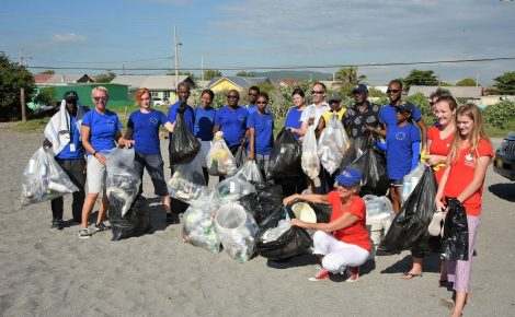Head of the European Union (EU) Delegation to Jamaica, Ambassador Malgorzata Wasilewska (second left), Canada's High Commissioner to Jamaica, Her Excellency Laurie Peters (stooping), and EU employees and other volunteers display bags of debris that were picked up off the Y-Knot Beach in Port Royal, Kingston, during the EU's clean-up exercise on Saturday (Oct. 20).