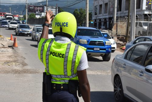 A police officer attached to the newly established Public Safety and Traffic Enforcement Branch (PSTEB) of the Jamaica Constabulary Force (JCF), directs traffic onto Constant Spring Road from West King's House Road as he assists with clearing a traffic jam at the intersection of the thoroughfares.
