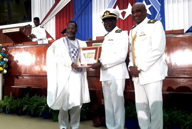 Minister of Education, Youth and Information, Senator the Hon. Ruel Reid (centre) receives a plaque from Caribbean Maritime University (CMU) Chancellor, His Royal Highness Drolor Bosso Adamtey I (left) during the CMU's 2018 graduation ceremony on Thursday (November 8) at the Jamaica Conference Centre, downtown Kingston. Sharing the moment is University President, Professor Fritz Pinnock. This year, approximately 350 students were conferred with master's, bachelor's and associate degrees and diplomas in a wide cross section of programmes.
