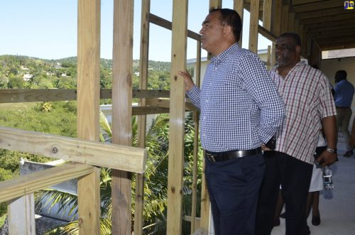 : Health Minister, Dr. the Hon. Christopher Tufton (left) and Regional Director at the Western Regional Health Authority (WRHA), Errol Greene (right), view construction work being undertaken at the Cornwall Regional Hospital, during a tour of a section of the facility in St. James on Friday, November 9.
