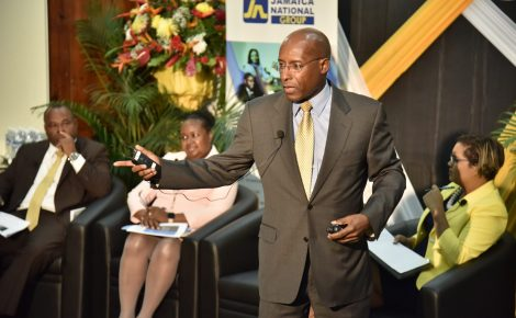 Executive Director of the Economic Growth Council, Senator Aubyn Hill (standing), addresses The Mico University College Education Conversation Series, held at the institution's Marescaux Road campus in St. Andrew yesterday (November 8). Listening (from left) are Investment Promotions Manager at JAMPRO, Ricardo Durrant; Chief Education Officer, Dr. Grace McLean; and Managing Director of the JN MSC Group, Onika Miller.
