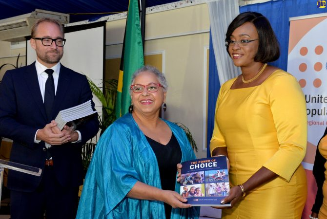 Wife of the Prime Minister and Champion for the Caribbean Woman-Caribbean Child (CARIWAC) Initiative, the Most Hon. Juliet Holness (right), is presented with a copy of the United Nations Population Fund (UNFPA) 2018 State of the World Population Report, during the Jamaica launch at the Terra Nova All-Suite Hotel in St. Andrew, by UNFPA Caribbean Sub-Regional Office Director and Representative, Alison Drayton, on Thursday (November 8). Mrs. Holness was the keynote speaker. At left is Deputy Director for the Caribbean Sub-Regional Office, Seth Broekman. The Report is titled 'The Power of Choice – Reproductive Rights and the Demographic Transition'.