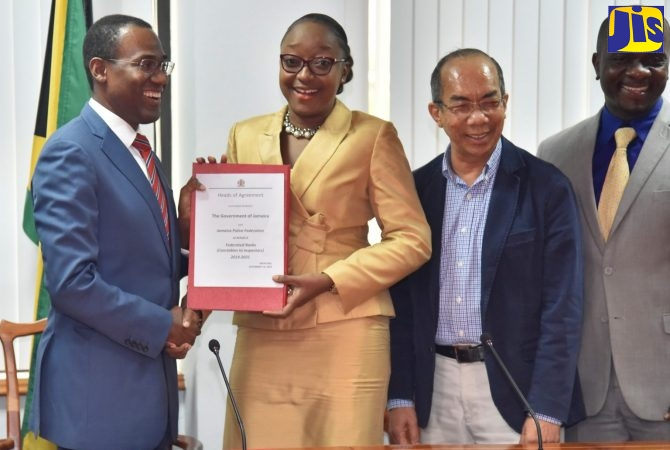 Finance and Public Service Minister, Dr. the Hon. Nigel Clarke (left); and Jamaica Police Federation (JPF) Chair, Corporal Arlene McBean (second left), display the Heads of Agreement for a four-year 16-per cent wage increase for rank and file members of the Jamaica Constabulary Force (JCF), covering the period 2017 to 2021. The signing took place at the Ministry's offices in Kingston on Friday (December 14). Minister of National Security, Hon. Dr. Horace Chang (second right); and JPF General Secretary, Inspector Sheldon Gordon, witnessed the proceedings.