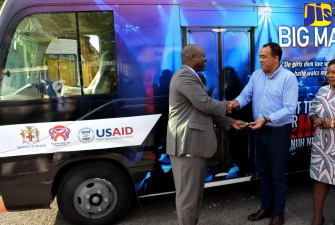 Minister of Health, Dr. the Hon. Christopher Tufton (centre), receives the keys to a mobile Human Immunodeficiency Virus (HIV) testing unit from United States Agency for International Development (USAID) Country Representative, Jason Fraser (left), during a handover ceremony at the Bustamante Hospital for Children, St. Andrew on Thursday (December 13). Looking on is Regional Director for the South East Regional Health Authority (SERHA), Maureen Golding.