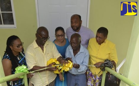 Minister of Local Government and Community Development,  Hon Desmond McKenzie (second left), cuts the ribbon to  officially hand over a self-contained studio unit to 75 year-old Gladstone Taylor (third left), in Williamsfield, Lime Hall, St. Ann on Friday, January 4. Sharing  the moment are (from left): Councillor for the Lime Hall Division, Genevor Gordon-Bailey; Member of Parliament for North East St. Ann and Minister of Labour and Social Security,  Hon. Shahine Robinson; Mayor of St. Ann's Bay and Chairman of the St. Ann Municipal Corporation, Councillor Michael Belnavis, and Councillor for the Bensonton Division, Lydia Richards.