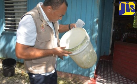 Minister of Health, Dr. the Hon. Christopher Tufton, examines a container during a tour of the Aldyar community in Westmoreland, on Friday ( January 4), in search of mosquito breeding sites.