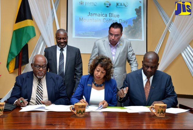 Minister without Portfolio in the Ministry of Economic Growth and Job Creation, Hon. Daryl Vaz (right, standing), observes as President of Jamaica Promotions Corporation (JAMPRO), Diane Edwards (second left, seated), signs a Memorandum of Understanding (MOU), at the JAMPRO offices in New Kingston on January 4. Also signing (from left) are Chairman of the Jamaica Agricultural Commodities Regulatory Authority (JACRA), Dennis Booth and Chairman of the Jamaica Coffee Exporters Association (JCEA), Norman Grant. Standing (at left) is Permanent Secretary in the Ministry of Industry, Commerce, Agriculture and Fisheries, Dermon Spence.