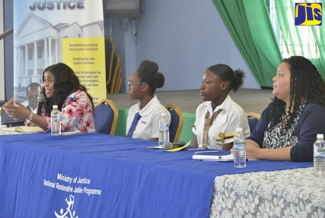 Coordinator of the Restorative Justice Unit in the Ministry of Justice, Dr. Kahilah Whyte (left), fields questions from students during a panel discussion at the Unit's Youth Town Hall Meeting at Sam Sharpe Teachers' College in Granville, St. James, on Wednesday (February 6). Other panellists (from second left) are Mount Alvernia High School student, Chrisann Morris; Anchovy High School student, Faydian Gordon; and Senior Director, Corporate Services Division, Ministry of Justice, Sandra Graham.