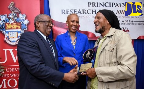 Minister without Portfolio in the Ministry of Finance and the Public Service, Hon. Fayval Williams, looks on as University of the West Indies (UWI) Mona Campus Pro Vice Chancellor and Principal, Professor Dale Webber (left), presents the Public Policy Award to Director of the Office of Social Entrepreneurship in the UWI's Faculty of Social Sciences, Dr. K'adamawe K'nife. Occasion was the UWI Annual Research Days awards ceremony at the Mona Visitors' Lodge on February 8.