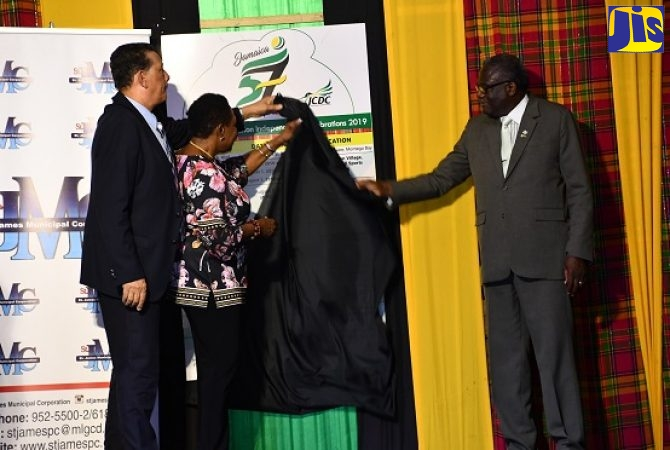 Minister of Culture, Gender, Entertainment and Sport, Hon. Olivia Grange (centre); Mayor of Montego Bay, Councillor Homer Davis (left) and Custos of St. James, Bishop the Hon. Conrad Pitkin, unveil the board depicting activities for the upcoming Emancipation and Independence celebrations in St. James . Occasion was the St. James Municipal Corporation's official launch for Emancipation and Independence activities in St. James, which was held at Sam Sharpe Square on Thursday (July 25).