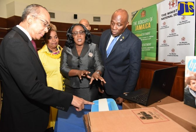 Minister of National Security, Hon. Dr. Horace Chang (left), inspects computer equipment donated to the Court Management Services by the Ministry as part of measures to further streamline the Traffic Ticket Management System (TTMS). The occasion was a handing over ceremony at the Supreme Court in downtown Kingston on Friday (December 13). Looking on (from 2nd left) are: Permanent Secretary in the Ministry of National Security, Dianne McIntosh; Director, Court Administration Division, Tricia Cameron-Anglin; Chief Judge of the Parish Courts, Chester Crooks (partly hidden); and Chief Justice, Hon. Bryan Sykes.