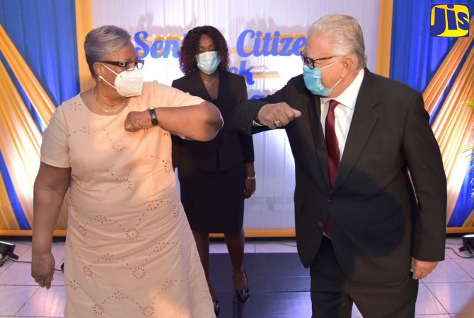 Minister of Labour and Social Security, Hon. Karl Samuda (right), greets Chairman of the National Council for Senior Citizens, Dorothy Findlayson (left), at the media launch of Senior Citizens' Week, at the Ministry in downtown Kingston on Friday (September 25). At centre is Principal Social Worker at the Council, Cassandra Morrison.