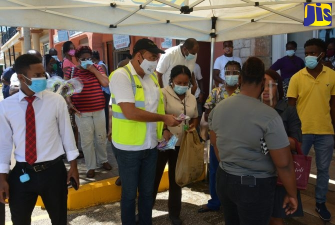 Minister of Health and Wellness, Dr. the Hon. Christopher Tufton, hands out face masks and health information to residents in Falmouth on Friday (September 25)