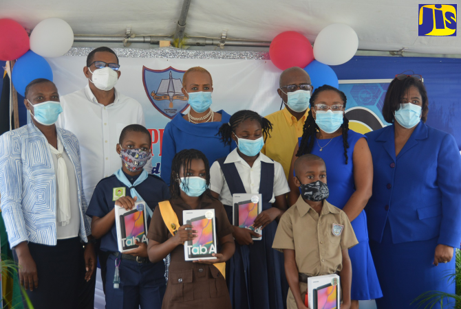 Education, Youth and Information Minister, Hon. Fayval Williams (back, third left), is joined by staff and students of Sandy Bay Primary & Junior High School in Hanover, during a ceremony for the presentation of 99 tablets to students of the institution on Thursday (November 19), under the Government's Tablets in Schools Programme.