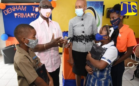 Minister of Local Government and Rural Development, Hon. Desmond McKenzie (second left) and Minister of Education, Youth and Information, Hon. Fayval Williams (centre), engaging with students following a ceremony for the handover of devices under the Tablets in Schools programme at the Denham Town Primary School in Western Kingston on November 20. The students (from left) are Andre Burke, St. Anne's Primary; Thaliah Allen, Chetolah Mel Nathan Educational Centre; and Camelia Howell, Denham Town Primary.