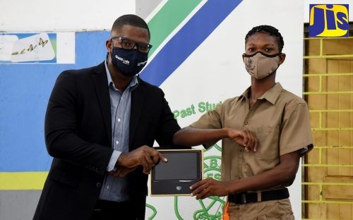 President of the Vauxhall High School Alumni Association, Jamaica Chapter, Timar Jackson (left), presents grade-nine student, Ishmael Small, with a tablet. The occasion was a ceremony for the handover of 61 tablets donated by the alumni association's New York chapter, at the institution's Windward Road address in Kingston, recently.