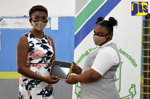 Vice Principal and past student of Vauxhall High School, Annette Campbell Burke (left), presents grade-eight student, Yolanda Forbes, with a tablet. The occasion was a ceremony for the handover of 61 tablets donated by the alumni association's New York chapter, at the institution's Windward Road address in Kingston, recently.