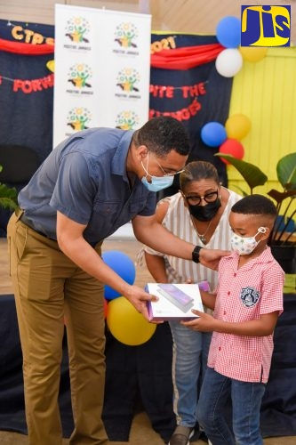 Prime Minister, the Most Hon. Andrew Holness (left), presents student of Clark's Town Primary School in Trelawny, Aiden Blake, with a tablet computer, during a ceremony at the school on Friday (July 2). Sharing in the occasion is Member of Parliament for Trelawny Southern, Marissa Dalrymple Philibert. The Prime Minister donated 40 tablets to students from seven primary-level schools in Southern Trelawny, through his Positive Jamaica Foundation.