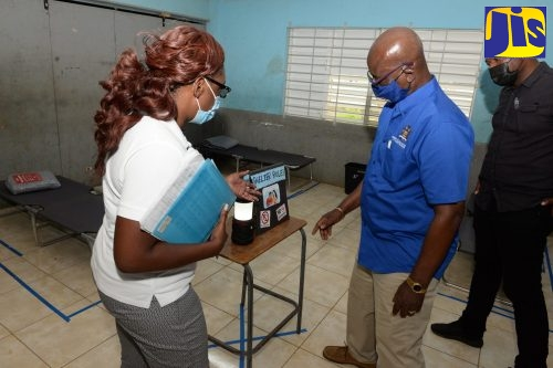 Minister of Local Government and Rural Development, Hon. Desmond McKenzie (centre), looks on as Clarendon Parish Disaster Coordinator, Eleanor Coombs-Waithe (left), highlights the shelter rules, during a visit to the Osborne Store Primary and Junior High School shelter in the parish on Friday (July 2). At right is Member of Parliament for South-Western Clarendon, Lothan Cousins.