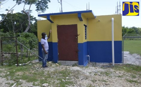 Principal of Little Bay Primary and Infant School in Westmoreland, Keron King, points to the institution's recently constructed water tank.