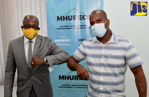 Minister of Housing, Urban Renewal, Environment and Climate Change, Hon. Pearnel Charles Jr. (left) greets Managing Director of Bundah and Sons Construction Ltd, André Bundah, at the contract signing ceremony for the Crooked River, Annotto Bay Hurricane Sandy Relocation Project, held at the Ministry's headquarters in Kingston, today (September 24).