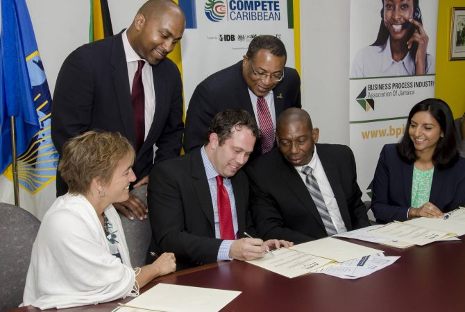 Industry, Investment and Commerce Minister, Hon. Anthony Hylton (right standing); and State Minister for Science, Technology, Energy, and Mining, Hon. Julian Robinson (right, standing), observe as Business Process Industry Association of Jamaica (BPIAJ) President, Yoni Epstein (2nd left, seated), signs the $56 million (US$500,000) grant agreement for the provision of technical assistance support under the Inter-American Development Bank's (IDB) Compete Caribbean programme, during Wednesday's (July 2), signing ceremony at the IDB's New Kingston offices. Also participating in the proceedings, from left (seated), are: Counsellor and Head, Development Cooperation, Canadian Department of Foreign Affairs, Trade and Development (DFATD) office in Jamaica, Marie Legault; IDB Senior Operations Specialist in Jamaica, Harold Arzu; and Acting Team Leader, Governance, United Kingdom Department for International Development (DFID) in Jamaica, Bhavna Sharma. Compete Caribbean is a private sector development programme that provides technical assistance grants and investment funding to support Micro, Small and Medium-size Enterprise (MSME) activities, among other engagements in 15 countries across the region. It is jointly funded by the IDB, DFID, and DFATD.