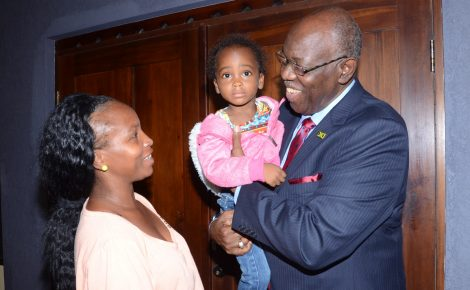 Health Minister, Hon. Dr. Fenton Ferguson (right) holds three year old Renique Holness (centre) during the launch of World Sickle Cell Day 2015 held on Friday, June 19 at the Faulty of Law Lecture Theatre at the University of the West Indies (UWI) Mona Campus in Kingston. Looking on is Renique's mother, Renee Davis (left)