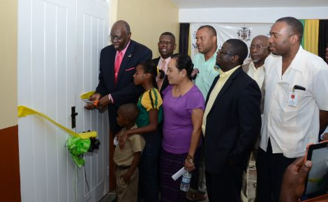Health Minister, Hon. Dr. Fenton Ferguson (left), performs the symbolic ribbon cutting exercise to formally open the Brainerd Health Centre in St. Mary, during Friday's (March 14) opening ceremony. Sharing in the occasion are: Member of Parliament for South East St. Mary, Dr. Winston Green (2nd left); Medical Officer of Health for St. Mary, Dr. San San Win (3rd left); Councillor for the Richmond Division, Richard Creary (centre); Chief Executive Officer, National Health Fund (NHF), Everton Anderson (3rd right); North East Regional Health Authority (NERHA) Chairman, Leon Gordon (2nd right); and Chief Medical Officer, Ministry of Heath, Dr. Kevin Creary. They are accompanied by pupils of the Brainerd primary and basic Schools.