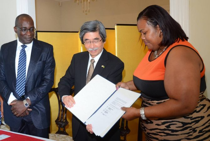 Education, Youth and Information Minister, Senator the Hon. Ruel Reid (left), looks on as Japan's Ambassador to Jamaica, His Excellency, Masanori Nakano (centre), and Warsop Primary School Principal, Stephanie Codling-Smith, display the signed agreement for a $10. 2 million grant to undertake upgrading works at the school. The grant signing and handing over ceremony was held at the Ambassador's residence in St. Andrew on March 24.