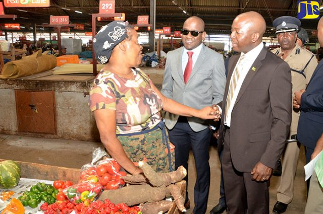 Minister of State in the Ministry of National Security, Senator the Hon. Pearnel Charles Jr. (right), greets vendor, Vivene Newman (left), during a tour of the Coronation Market in downtown Kingston today (January 27), following the staging of a pop-up information clinic at the market. Others (from second left) are: Councillor Dwayne Smith and Assistant