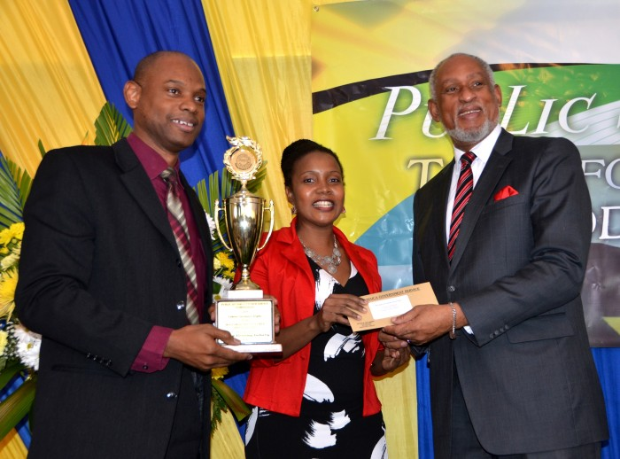 Cabinet Secretary, Ambassador, Hon. Douglas Saunders (right) presents the trophy and a $200,000 cheque to the Chief Executive Officer (CEO) of the Firearm Licensing Authority  (FLA), Dr. Kenrey Wedderburn (left) and the Director of Applications and Certification at the FLA, Miss Letine Allen, at the Public Sector Customer Service Competition at the Terra Nova All-Suites Hotel on Friday, October 9. The FLA was recognised as being the Most Improved Entity in the competition put on by the Cabinet Office.