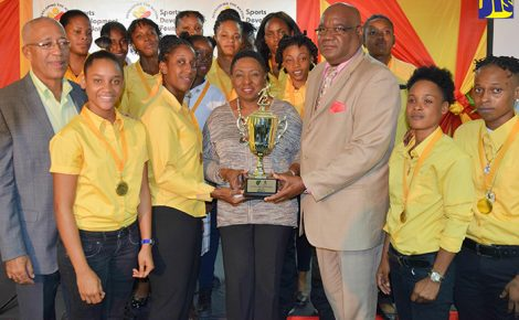 Minister of Culture, Gender, Entertainment and Sport, the Honourable Olivia Grange shared a photo opportunity with Barbican FC, winners of the 2016 JFF/SDF Women's Premier League, at the Awards Ceremomy yesterday at the JFF Headquarters. The moment was also shared with (left) Coach, Charles Edwards and Bruce Gaynor, Vice President of the JFF.
