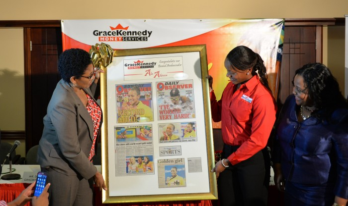 Minister with responsibility for Sport, Hon. Natalie Neita Headley (right), looks on as World 100-metre breaststroke Champion, Alia Atkinson (centre), is presented with a plaque by Senior Marketing Manager at GraceKennedy Money Services (GKMS), Sandra Forbes (left). Occasion was a welcome home reception, held today (January 9), at the Norman Manley International Airport, in Kingston.